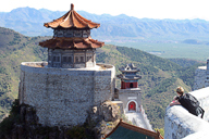A view of a temple high on a hill, with mountains behind