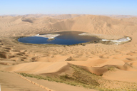 A desert lake, seen from the peak of a tall dune in the Badain Jaran Desert, Inner Mongolia