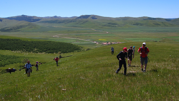 Hikers climbing up into the hills of the Bashang Grasslands, Hebei Province