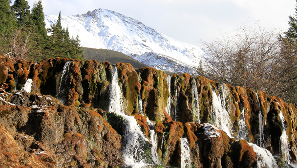 Mountains behind a waterfall in Munigou Park, Sichuan, China