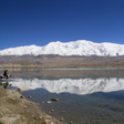 Snow covered mountains reflected in Lake Karakul, Xinjiang Province