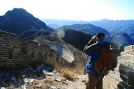 A hiker using binoculars to get a closer look at a stretch of Great Wall