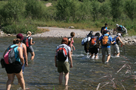 Hikers crossing a river