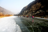 Hikers making their way down a frozen river