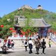 People walking toward the entrance of Yajishan Temple, with the temples seen on the mountain in the background
