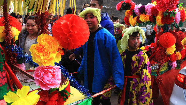 Performers and their float join a parade in Nuanquanzhen