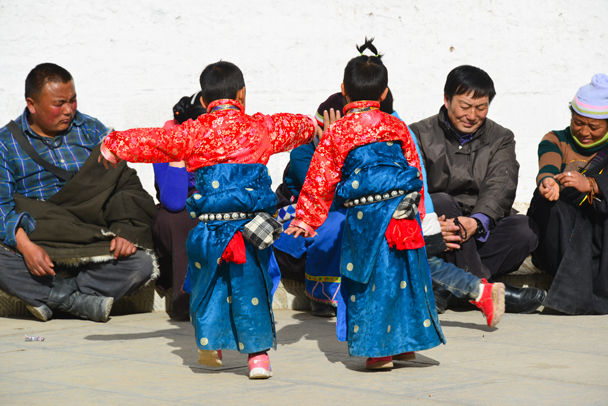 Two little kids dressed up for a performance (Photo by Dennis) - Labrang Monastery and Tibetan New Year, 2016/02