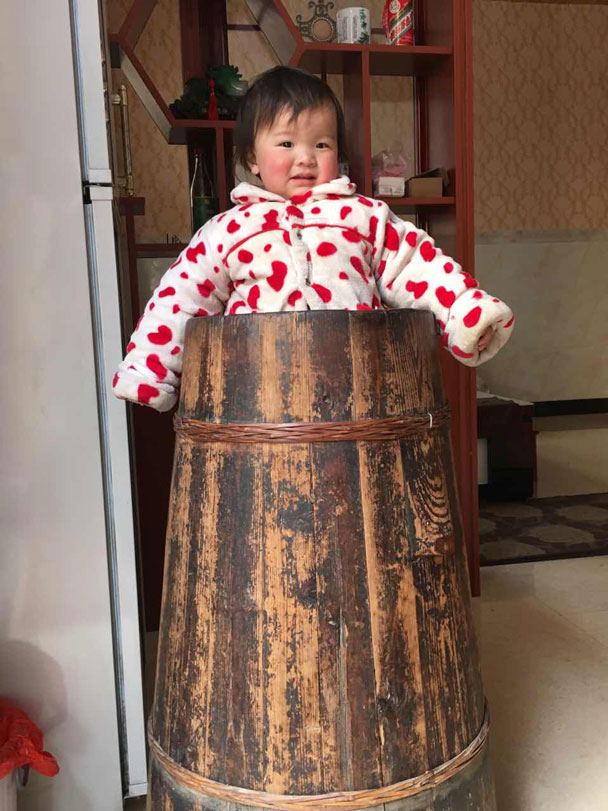 The bucket is heated from below, keeping the baby warm. The bucket also keeps the baby from getting up to mischief! - Wuyuan, Jiangxi Province, 2016/03