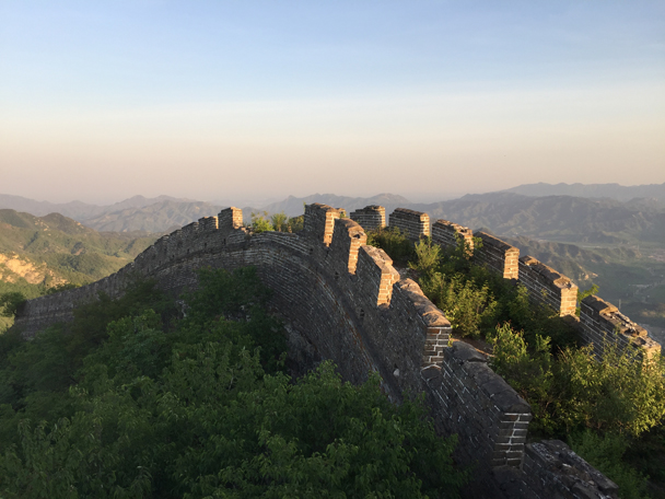 The last of the sun is shining on the Great Wall Spur. Smoggy Beijing is way in the background - Camping at the Great Wall Spur, 2016/05