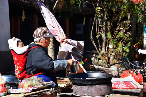 Preparing local snacks with her grandchild on her back - Lijiang and Shangri-La, Yunnan Province, November 2016