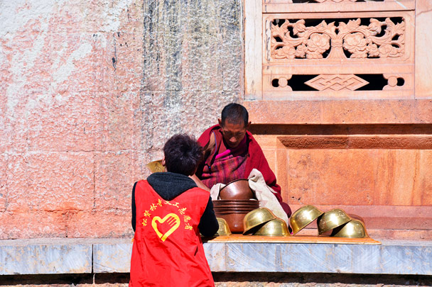 A monk cleaning bowls which are used to accept offerings - Lijiang and Shangri-La, Yunnan Province, November 2016