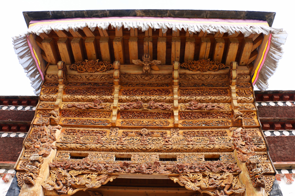Carved ornamentation above a door of one of the halls in the monastery - Labrang Monastery and Xiahe, Gansu