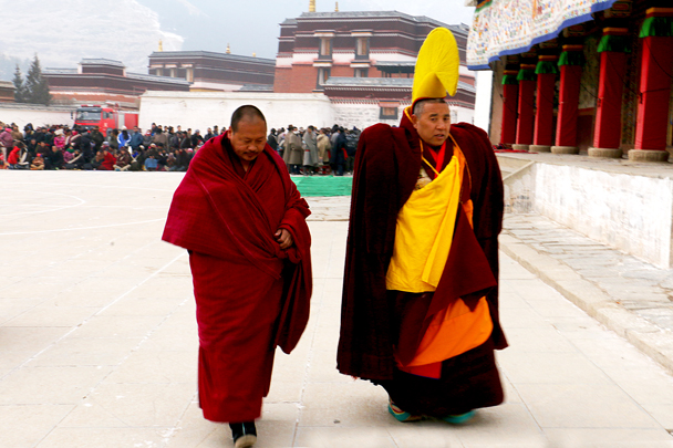 The yellow hat and sash mean he's a master, and the other monk is his assistant - Labrang Monastery and Xiahe, Gansu