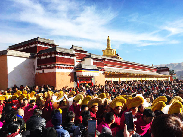 The monks with the special hats are carrying the <i>thangka</i> tapestry to be unveiled - Unveiling the Buddha at Labrang Monastery, 2018/02