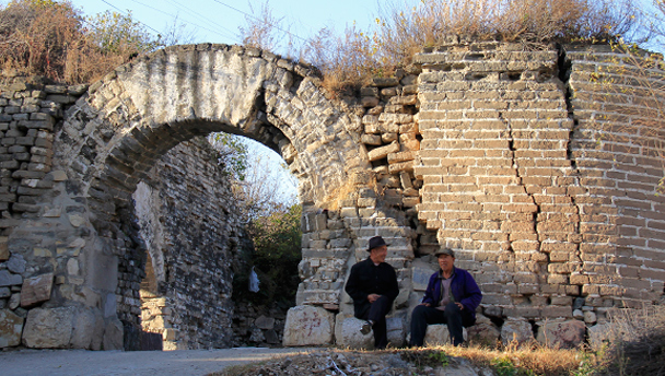 Two elderly villagers sit in front of a large gate in a thick stone wall