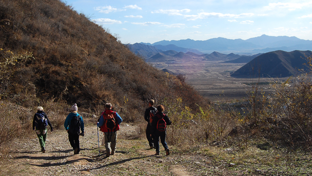 Hikers on a road, with a broad view of a plain in front