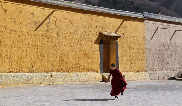 A young monk running to class