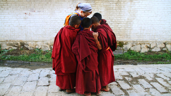 Young monks crowding for a look at a photo
