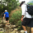 Hiking kids cross stepping stones over a river in Intelligence Valley