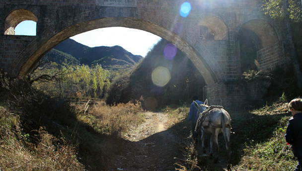 Hikers - and a donkey - follow a village road beneath an aqueduct