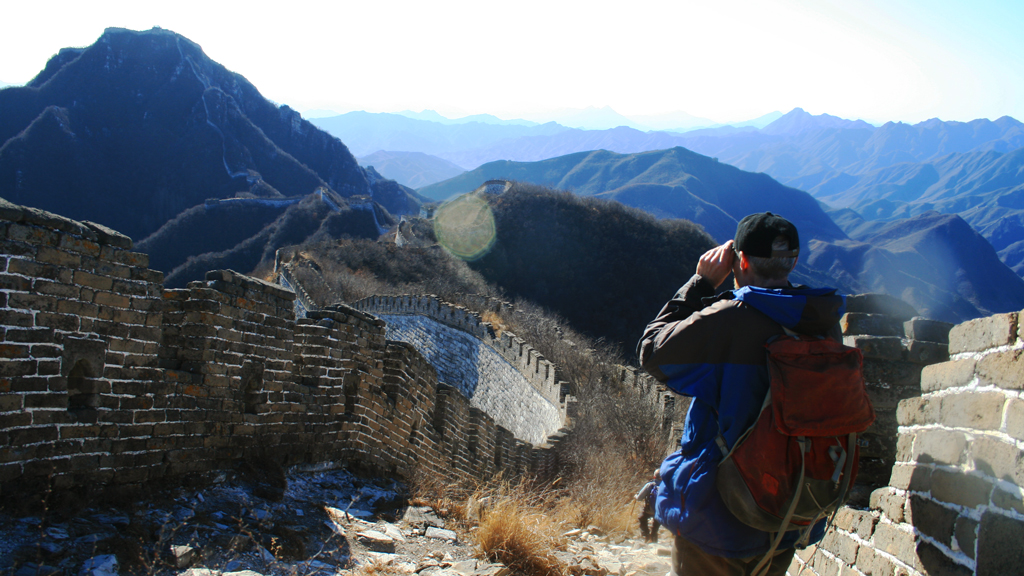Nine Eyes Tower Great Wall | A hiker using binoculars to get a closer look at a stretch of the Jiankou Great Wall