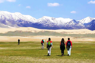 Hiking in grassy meadows near Qinghai Lake, with the Qilian Mountains seen in the distance