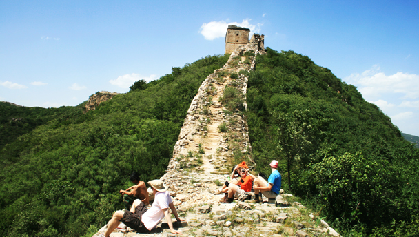 Switchback Great Wall | Hikers sitting on the unrestored wild wall below a Great Wall tower