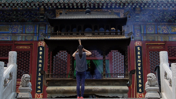 A visitor to Tanzhe Temple raises burning incense in prayer