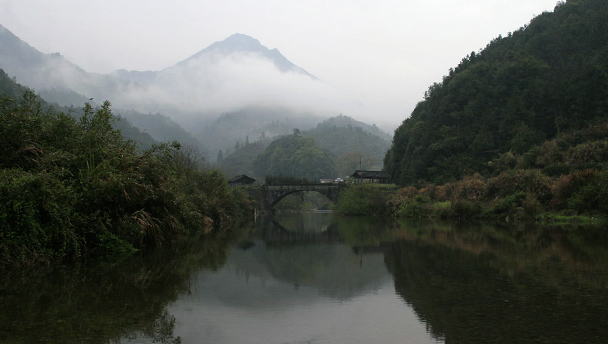 An arched bridge crosses a lake, with mountains behind