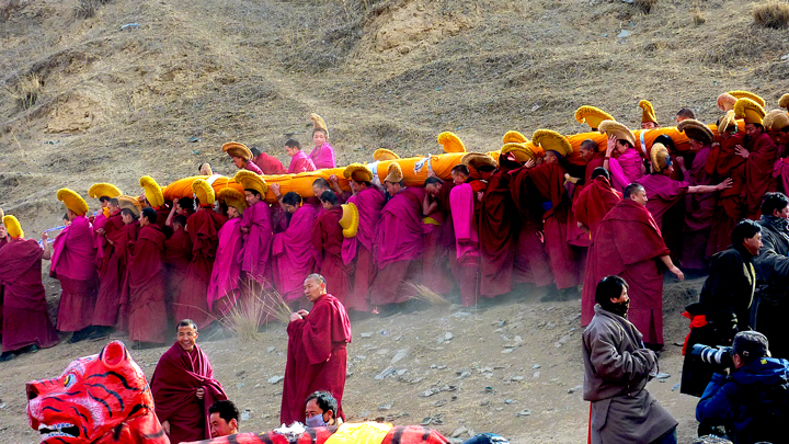 A rolled thangka is carried towards the hills