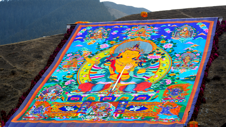The thangka is displayed on the hillside