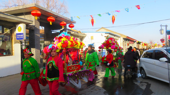 Performers and their float on their way to a parade in Nuanquanzhen