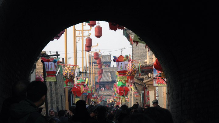 A busy street in Nuanquanzhen, seen through an arched gate in the city walls